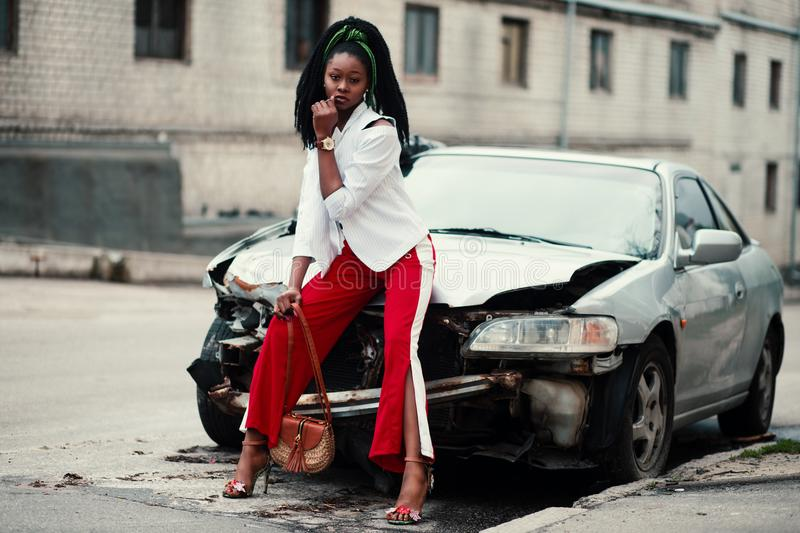 Woman With White Long-sleeved Shirt, Red ,and White Slit Pants and Pair of Black Open-toe D'orsay Heel Sandals Sitting on Wre stock photography