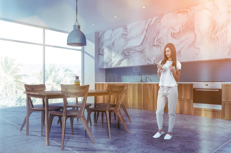 Woman in white marble and blue kitchen. Young woman with coffee standing in stylish kitchen interior with white and blue walls, wooden countertops, white marble stock image