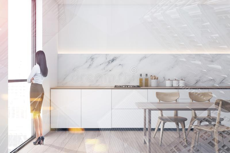 Woman in white and marble kitchen stock photo