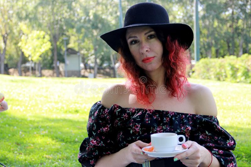 woman with a white mug and saucer in her hand. a woman with red curls of hair, dressed in a black dress and a black hat, with a stock image