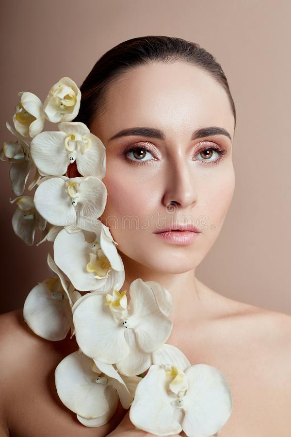 Woman with white Orchid near face girl with beautiful bright makeup pink lipstick. Gentle art portrait Advertising cosmetics. Professional makeup art, glitter royalty free stock images
