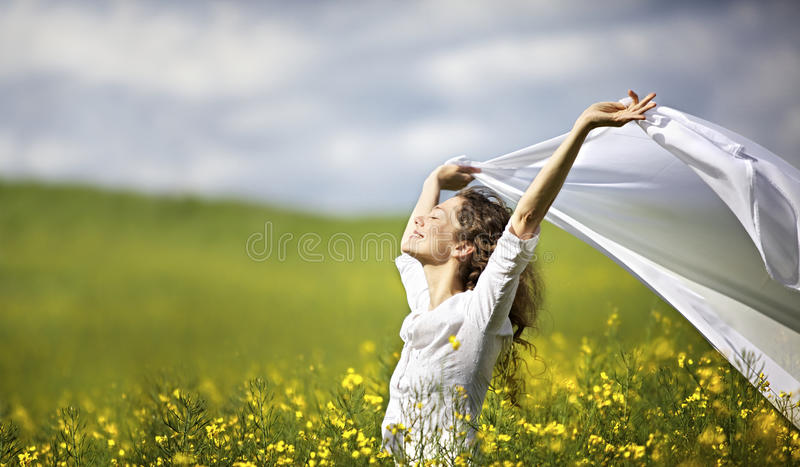 Woman with white piece of cloth in wind. Young happy woman standing in yellow rapeseed field holding a white piece of cloth in the wind expressing freedom stock photography