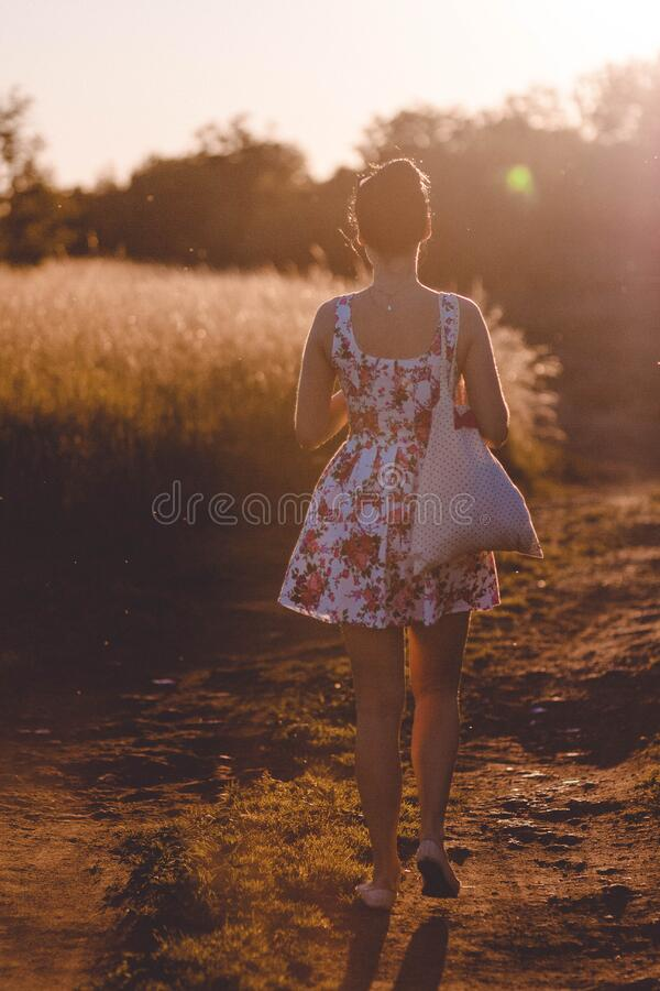 Woman in White and Pink Floral Sleeveless Dress Walking on Brown Road during Sunlight royalty free stock image