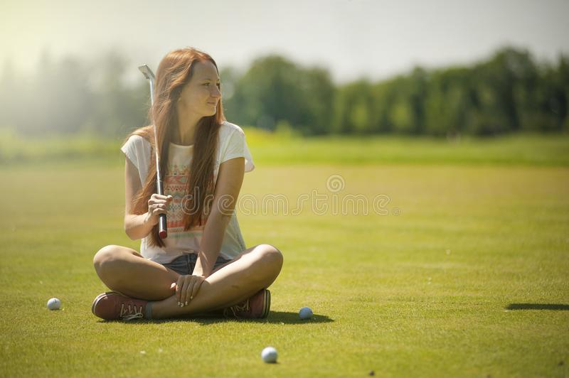 Woman in White Scoop-neck Shirt and Blue Shorts Holding a Golf Club Sitting on Golf Field stock images