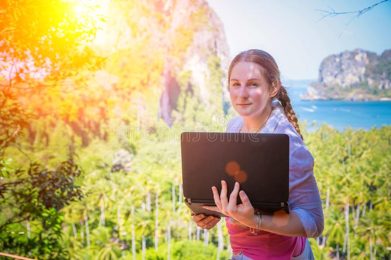 Woman in white shirt with black laptop on the top of cliff. Distance working, touristic routes creating. View on the sea,. Mountains and tropical jungles at royalty free stock image