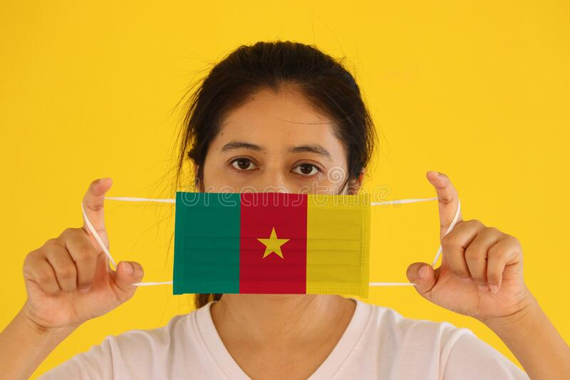 A woman in white shirt with Cameroon flag on hygienic mask in her hand and lifted up the front face on yellow background. Tiny. Particle or virus corona or royalty free stock images