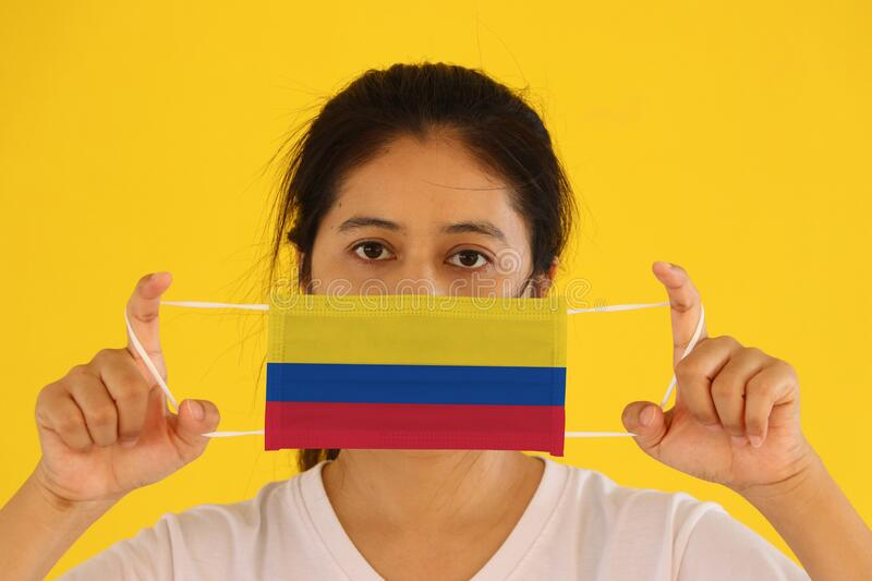 A woman in white shirt with Colombia flag on hygienic mask in her hand and lifted up the front face on yellow background. Tiny. Particle or virus corona or stock photo