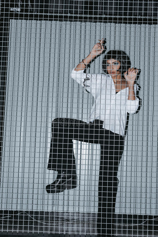 Woman in white shirt with cuffs standing behind grate. And looking away stock photos