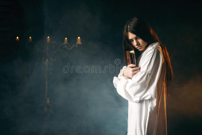 Woman holds spellbook in hands, witchcraft. Woman in white shirt holds spellbook in hands, candles and smoke on background. Dark magic ritual, occultism and stock photo