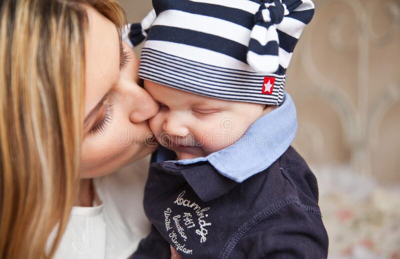 Woman In White Shirt Kissing Baby With Black And White Stripe Knit Cap Free Public Domain Cc0 Image