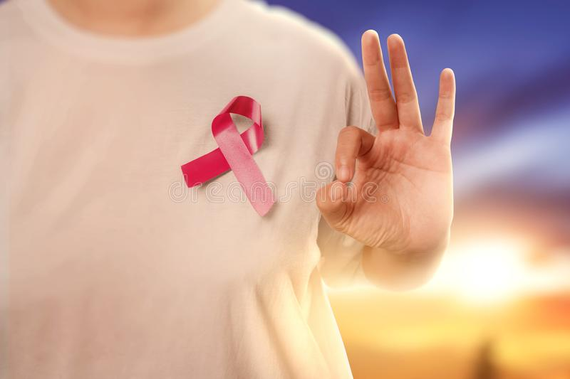 Woman in a white shirt with a pink ribbon and showing an OK sign with a sunset sky background royalty free stock photo