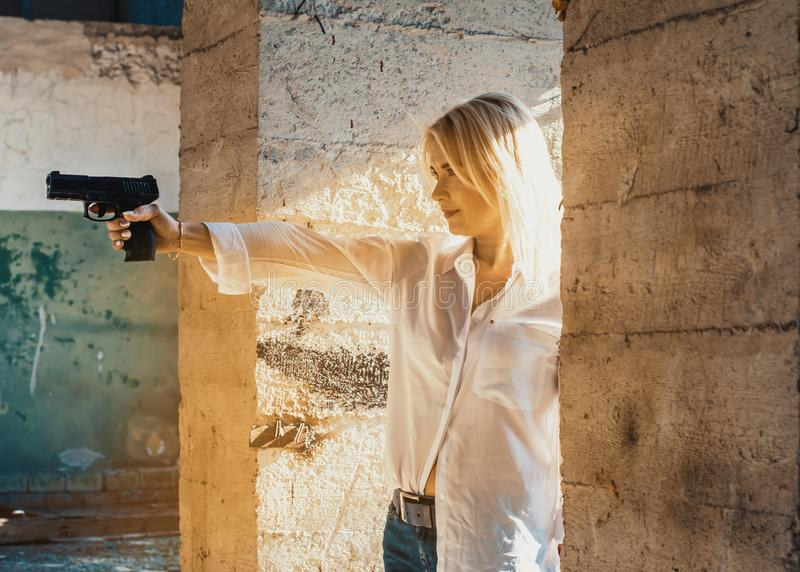 Woman in a white shirt shoots a pistol in an abandoned building from around the corner.  royalty free stock photo