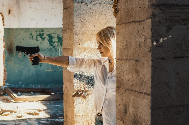 Woman in a white shirt shoots a pistol in an abandoned building from around the corner.  stock images