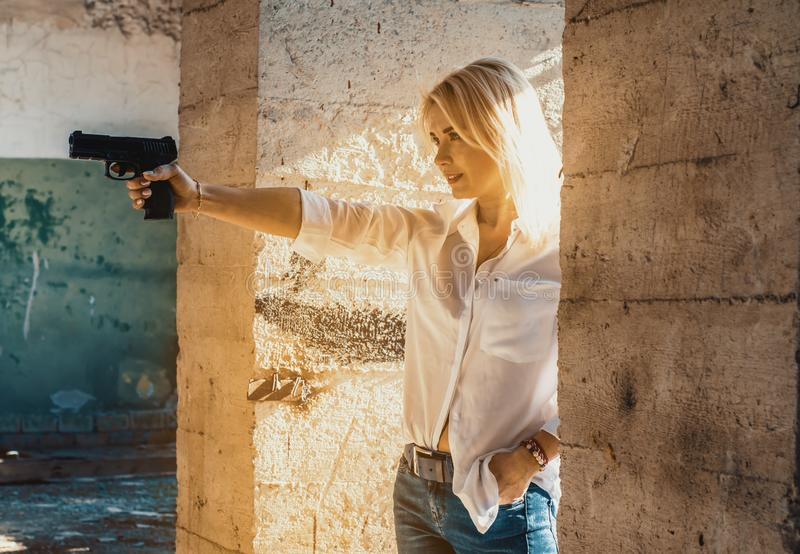 Woman in a white shirt shoots a pistol in an abandoned building from around the corner.  stock image
