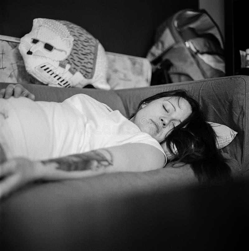 Woman in White Shirt Sleeping on Gray Fabric Sofa stock photos