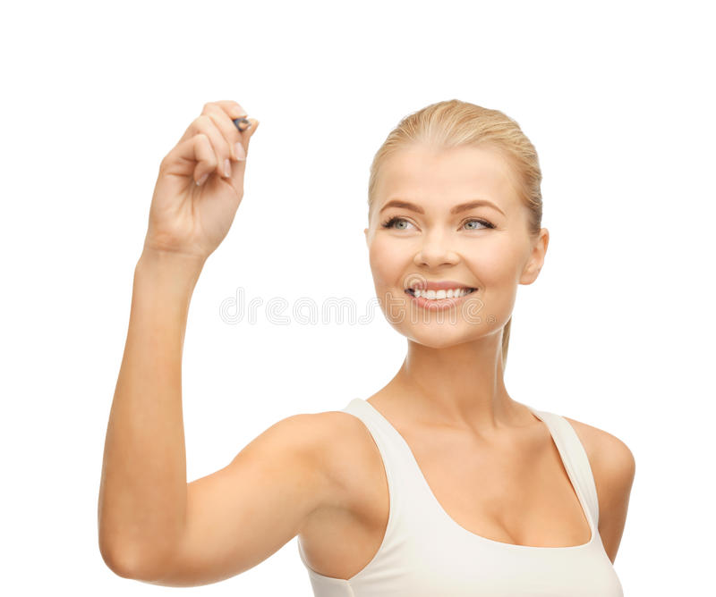 Woman in white shirt writing in the air. Smiling woman in white shirt writing in the air stock photo