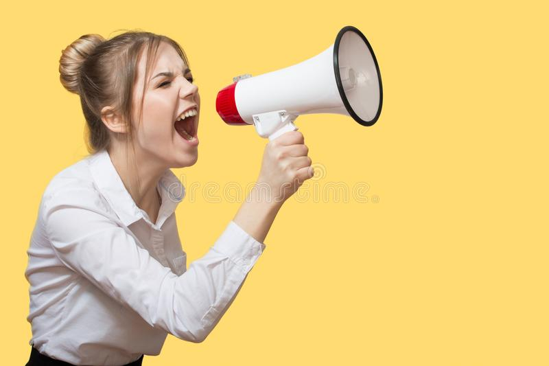Woman screaming into a megaphone stock photography