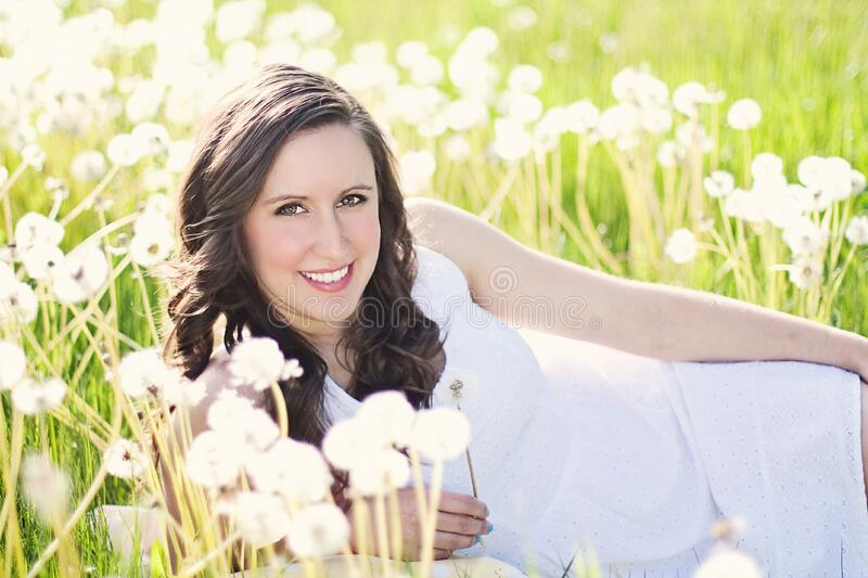 Woman in White Sleeveless Dress Lying on Green Grass Field royalty free stock photo