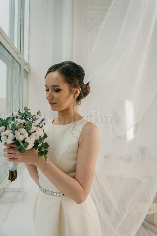 Woman in White Sleeveless Gown Holding White Flower Bouquet Infront of Window royalty free stock images