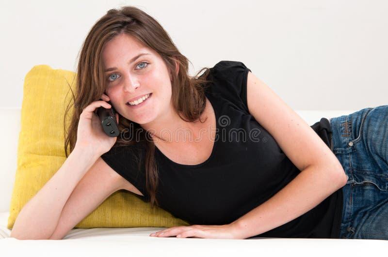Woman on a white sofa making a phone call stock photo