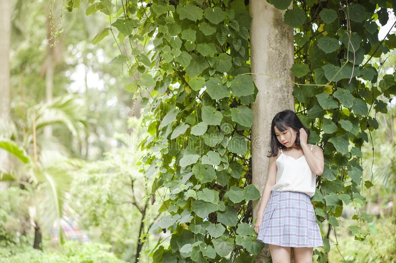 Woman in White Spaghetti Strap Top and Gray Skirt Standing in Front of Tree royalty free stock photo
