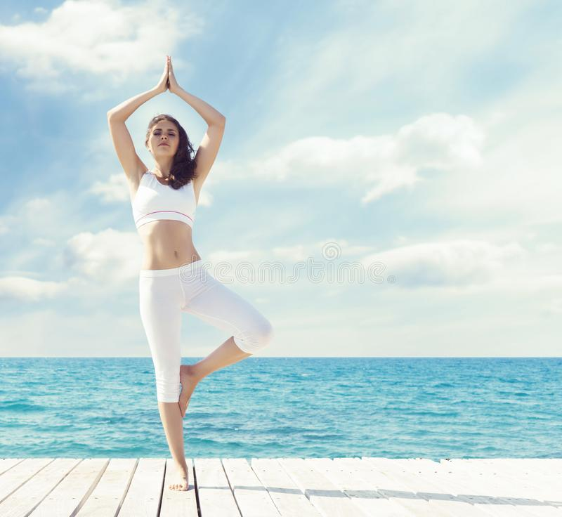 Woman in white sportswear doing yoga on a wooden pier. Sea and royalty free stock image