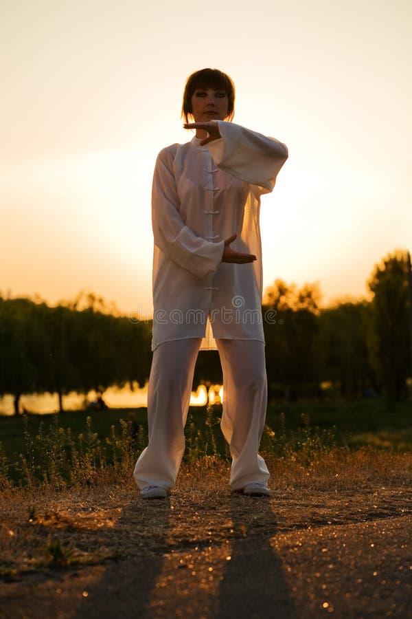 Woman in white suit make's taiji chuan - 12 stock photos
