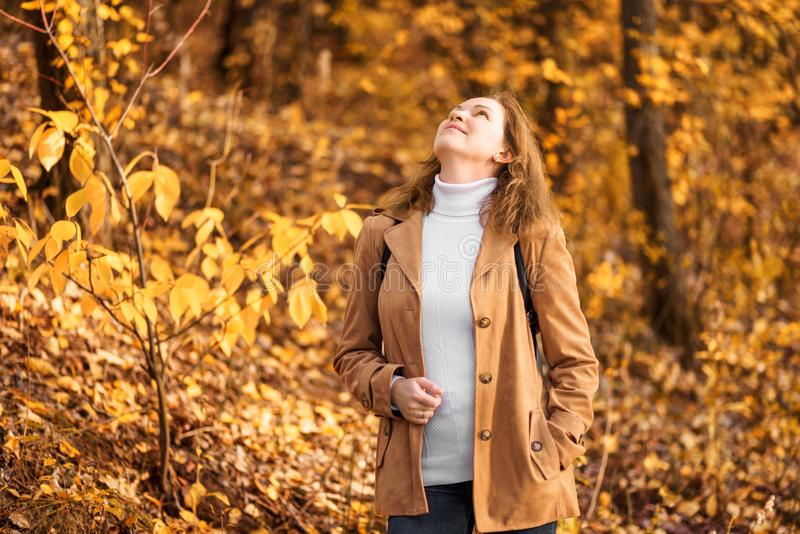Woman in white sweater and beige jacket in autumn park. Happy adult girl walking in autumn forest stock photography