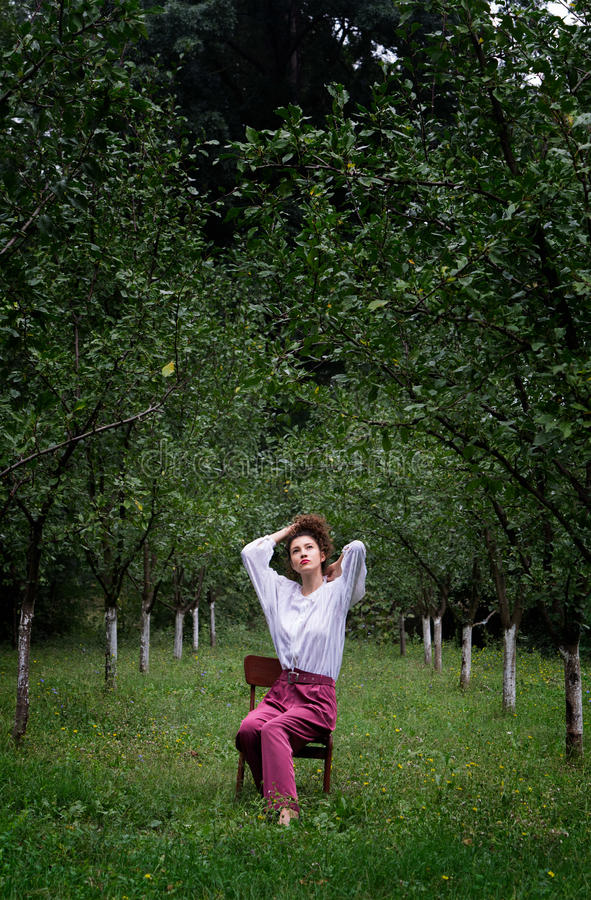 Download Woman In White Sweater Sitting On Brown Wooden Chair Stock Photo - Image of trees, photo: 83018072