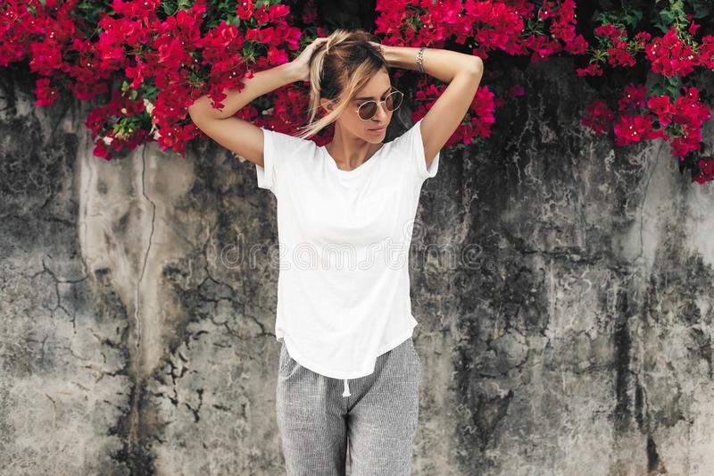 Woman in white t-shirt on grey background with spring flowers royalty free stock photos