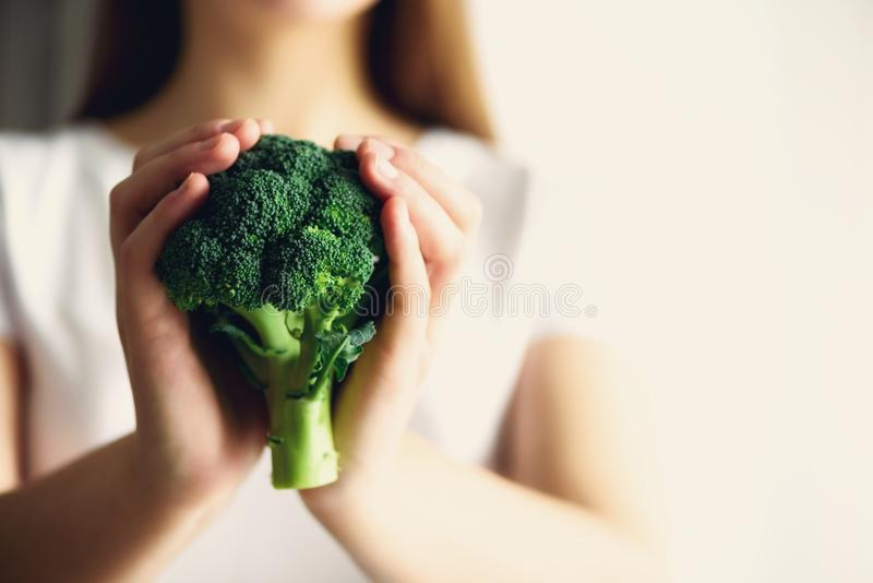 Woman in white T-shirt holding broccoli in hands. Copy space. Healthy clean detox eating concept. Vegetarian, vegan, raw royalty free stock images