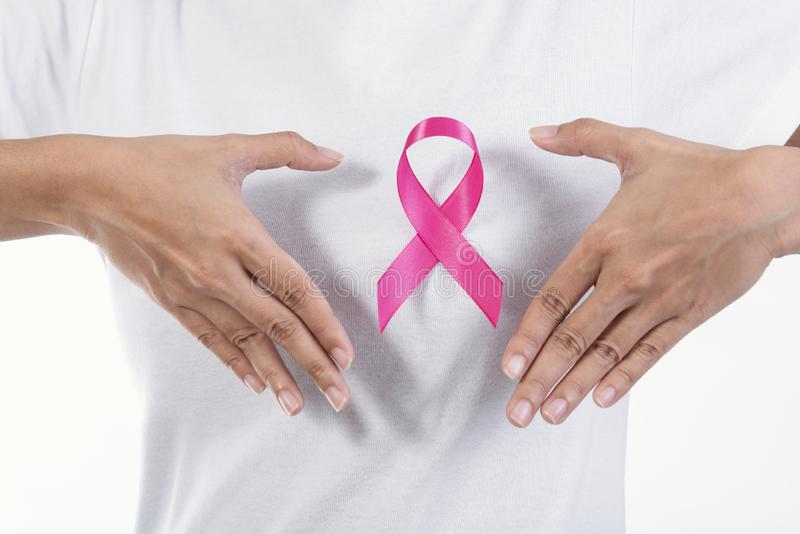 Woman in white t-shirt with pink ribbon on chest. supporting royalty free stock image