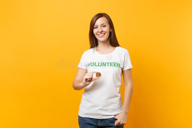 Woman in white t-shirt with written inscription green title volunteer hold bitcoin, metal coin future currency isolated stock photography