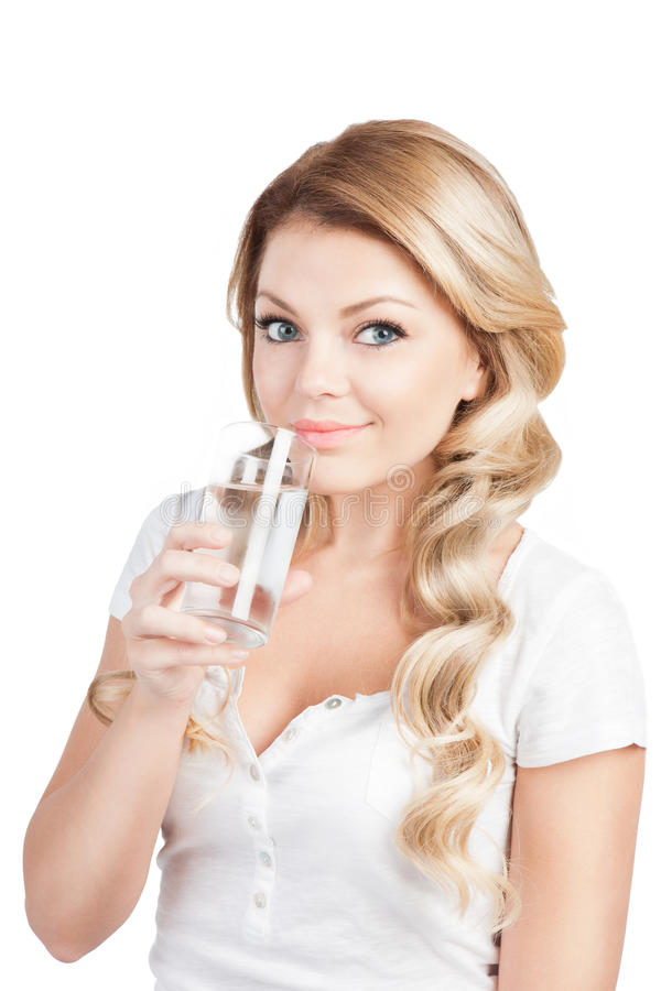 Woman in white T-short holding glass of water. Beautiful blonde long-haired girl is drinking water from glass on white. Studio shot royalty free stock photography
