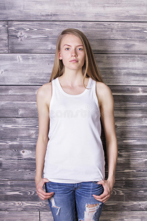 Woman in white tank top. Attractive young woman wearing plain white tank top and jeans on wooden plank background. Mock up royalty free stock images