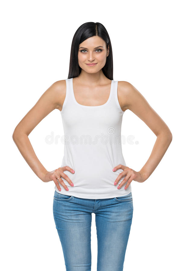 Woman is in a white tank top and blue denims. Isolated. Brunette woman is in a white tank top and blue denims. Isolated royalty free stock image