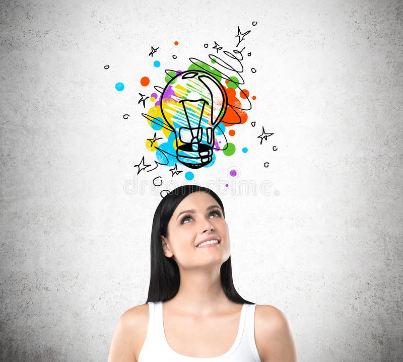 Woman in white tank top and colorful light bulb sketch. Smiling woman in white tank top standing under colorful light bulb sketch drawn on concrete wall above stock photos