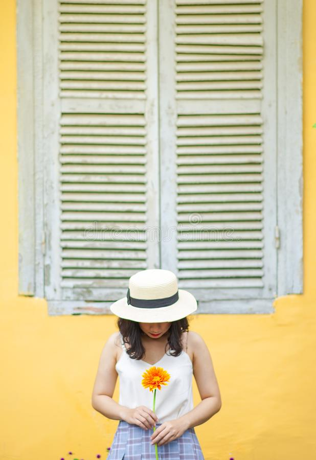 Woman in White Tank Top Holding Sunflower Near Window Outdoors stock photo
