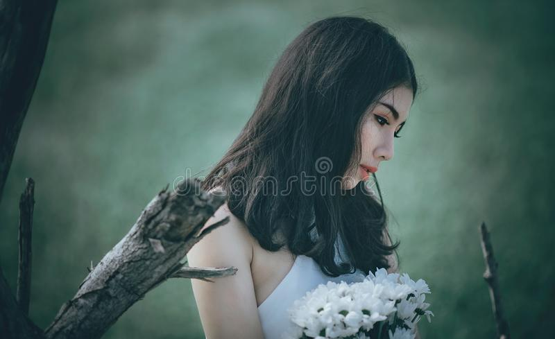 Woman in White Top Holding Bouquet of White Petaled Flowers While Looking Down stock photo