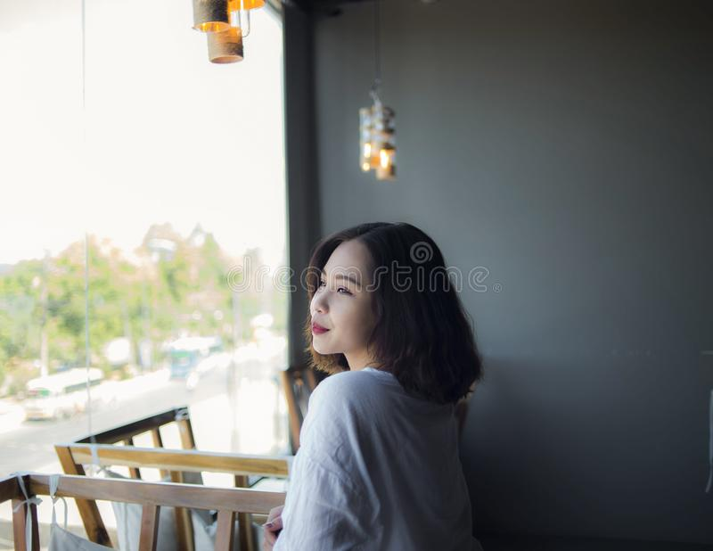 Woman in White Top Looking Outside Window royalty free stock image