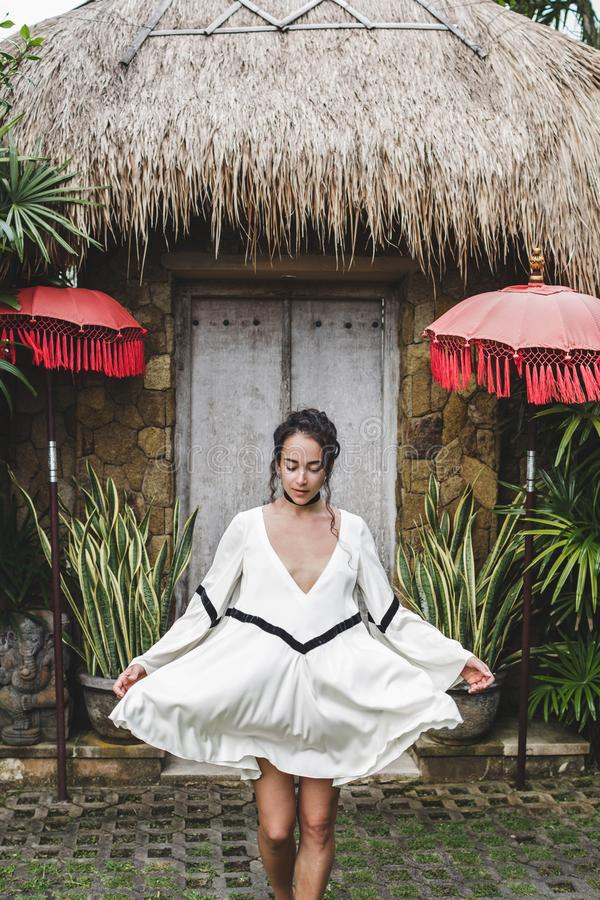 Woman in white tunic on background traditional balinese architecture. Young woman in white tunic in Ubud village with traditional balinese architecture. Style of royalty free stock photo
