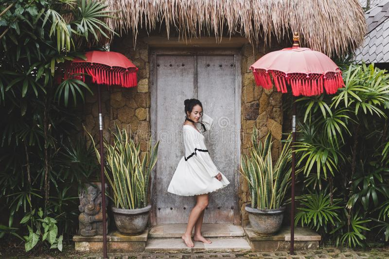Woman in white tunic on background traditional balinese architecture. Young woman in white tunic in Ubud village with traditional balinese architecture. Style of stock photo