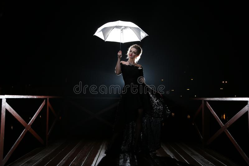 Woman with white umbrella in flash lights and rain drops royalty free stock images