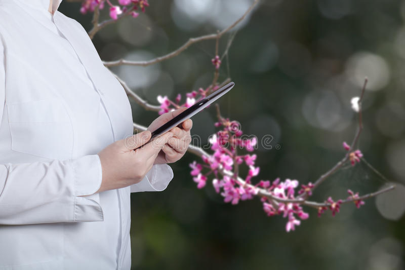 A woman in a white uniform robe with electronic device in her ha. Nds in front of a blurred background royalty free stock images