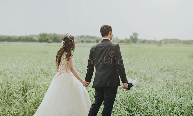 Woman in White Wedding Dress Holding Hand to Man in Black Suit royalty free stock image