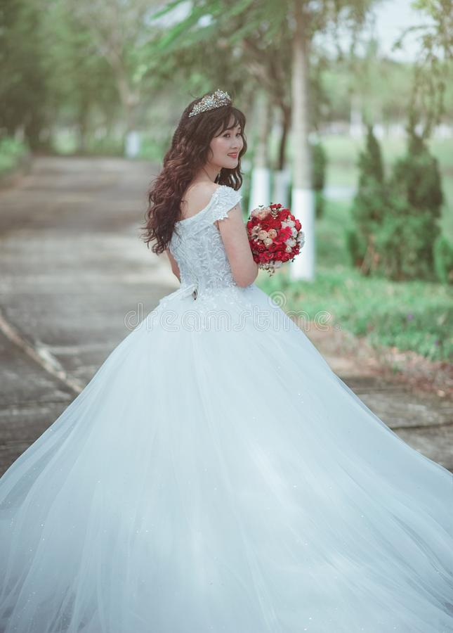 Woman in White Wedding Dress Holding Red Bouquet stock photo