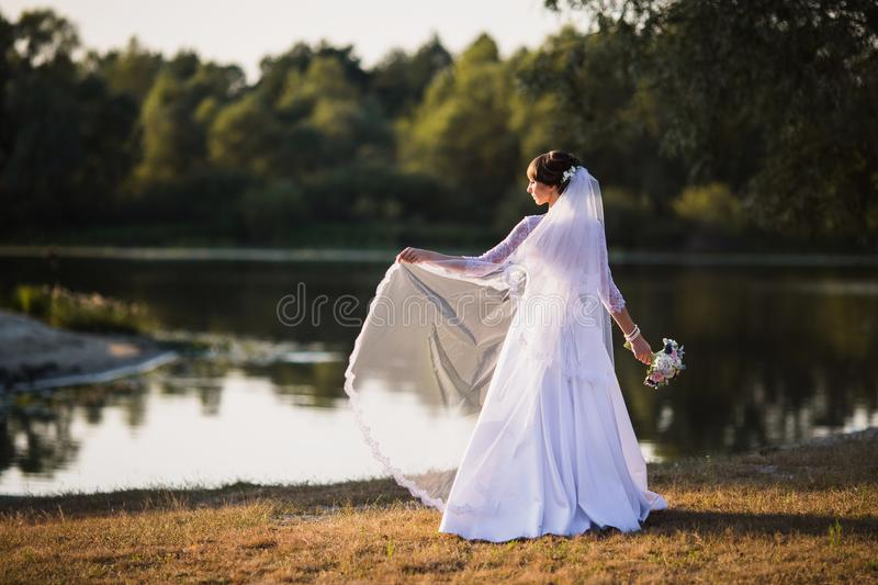 Woman in a white wedding dress on nature background stock photos