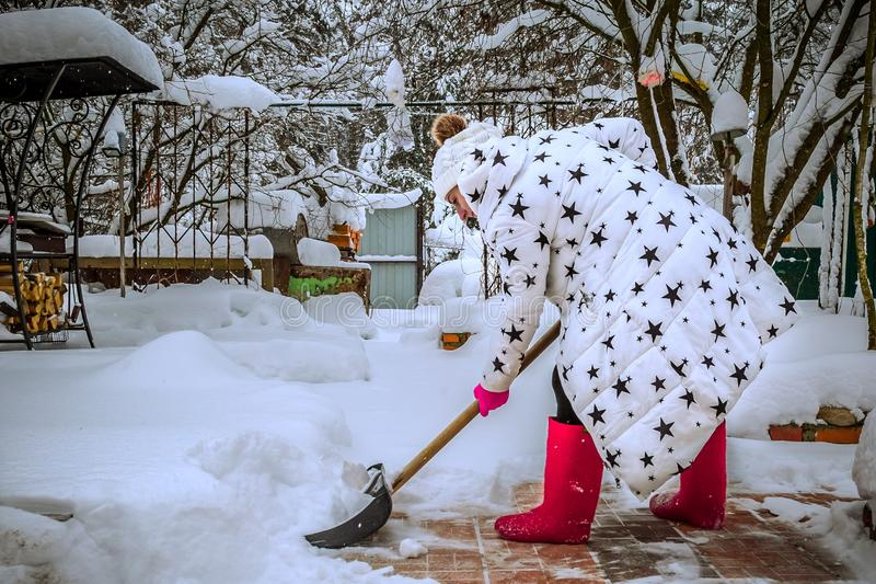 Woman in a white winter jacket and red shoes. Clears the road from snow after heavy snowfall. The girl removes snow with a shovel stock images