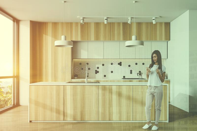 Woman in white and wooden kitchen with island royalty free stock photography