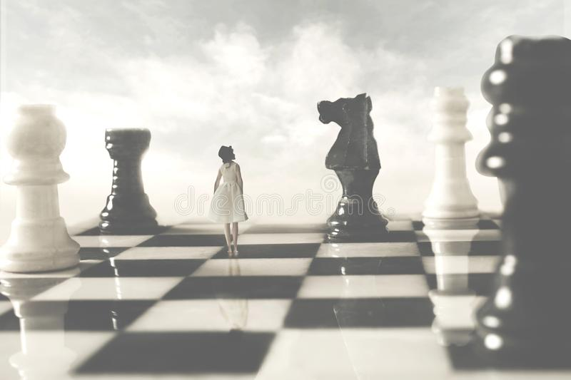 Woman who is allied with the white chessboards looks suspiciously at her black rival stock image